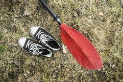 Les espadrilles et les palettes noires se trouvent sur l'herbe sèche et les feuilles dedans tôt Images libres de droits