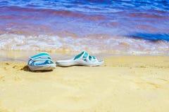 Les espadrilles faites de caoutchouc sont sur la plage Images libres de droits
