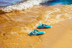 Les espadrilles faites de caoutchouc sont sur la plage Images stock