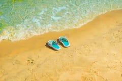 Les espadrilles faites de caoutchouc sont sur la plage Photos libres de droits