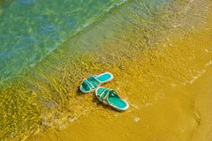 Les espadrilles faites de caoutchouc sont sur la plage Image libre de droits