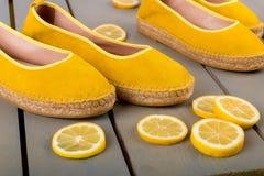 Les espadrilles jaunes chausse près des tranches de citron sur le fond en bois Fin vers le haut Photo libre de droits