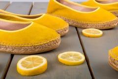Les espadrilles jaunes chausse près des tranches de citron sur le fond en bois Fin vers le haut Photo stock