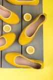 Les espadrilles jaunes chausse près des tranches de citron sur le fond en bois Vue supérieure Image stock