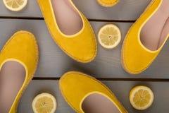 Les espadrilles jaunes chausse près des tranches de citron sur le fond en bois Vue supérieure Images libres de droits