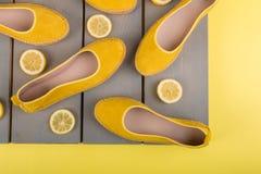 Les espadrilles jaunes chausse près des tranches de citron sur le fond en bois Vue supérieure Photo stock
