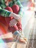 Les espadrilles jaunes sur des jambes de fille dans le hippie dénomment se reposer sur le Ben Photo stock