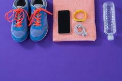 Les espadrilles, la bouteille d'eau, la serviette, le téléphone portable avec des écouteurs et la forme physique se réunissent Image stock