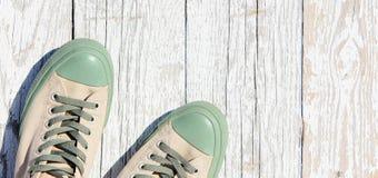 Les espadrilles lacées se tiennent sur un fond en bois blanc Été, vue supérieure de chaussures de sports Photos stock