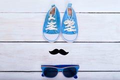 Les espadrilles, les lunettes de soleil et la moustache bleues du ` s d'enfant se trouvent sur un OE blanc Photo libre de droits