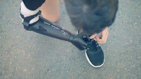 Les espadrilles que les dentelles de ` obtiennent ont attaché par un homme avec une main prosthétique