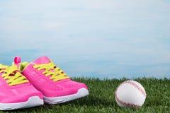 Les espadrilles roses avec les dentelles jaunes se tiennent sur l'herbe près de la boule Photo stock