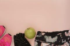 Les espadrilles roses femelles, les chaussures de sport, les guêtres, la pomme verte et les gants dans l'appartement étendent le  Image stock