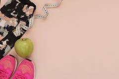 Les espadrilles roses femelles, les chaussures de sport, les guêtres, la pomme verte et le mètre dans l'appartement étendent le s Image libre de droits