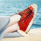 Les espadrilles rouges de mode sur la fille et la mer aménagent en parc Images stock