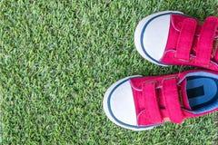 Les espadrilles rouges de tissu de plan rapproché de l'enfant sur l'herbe artificielle verte ont donné au fond une consistance ru Images libres de droits