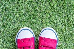 Les espadrilles rouges de tissu de plan rapproché de l'enfant sur l'herbe artificielle verte ont donné au fond une consistance ru Photos stock