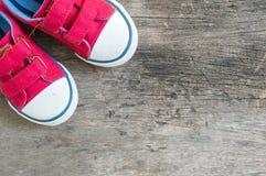Les espadrilles rouges de tissu de plan rapproché de l'enfant sur le vieux plancher en bois ont donné au fond une consistance rug Photographie stock