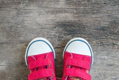 Les espadrilles rouges de tissu de plan rapproché de l'enfant sur le vieux plancher en bois ont donné au fond une consistance rug Photos stock