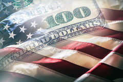 Les Etats-Unis diminuent et les dollars américains Drapeau américain soufflant en le vent et 100 dollars de billets de banque à l Photographie stock libre de droits