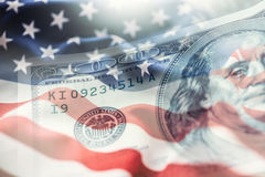 Les Etats-Unis diminuent et les dollars américains Drapeau américain soufflant en le vent et 100 dollars de billets de banque à l Image stock