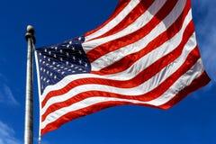 LES Etats-Unis Enroulez le drapeau enflé les Etats-Unis d'Amérique au-dessus du fond de ciel Images stock