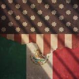 Les Etats-Unis et drapeau du Mexique divisé sur un mur Photo stock