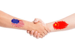 Les Etats-Unis et mains de la Chine secouant avec des drapeaux Images stock