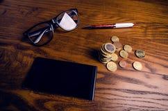 Les euro pièces de monnaie et monnaie fiduciaire d'argent se sont concentrées en verres sur une table en bois Finances et concept Photos libres de droits