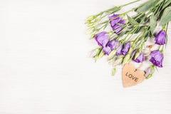 Les eustomess sensibles fleurit sur un fond en bois blanc Coeur et fleurs en bois Photographie stock libre de droits