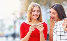 Les expositions de femme à un téléphone portable est quelque chose à son amie photographie stock libre de droits