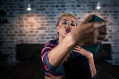 Les expositions peu communes de jeune femme embrassent in camera du smartphone à l'appartement élégant Photo libre de droits