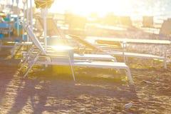 Les fainéants sur la plage ont abandonné le bord de la mer au lever de soleil étonnant Image stock