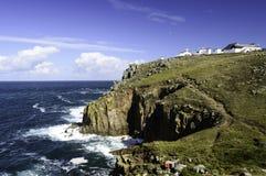 Les falaises et les vagues de rupture aux terres finissent dans les Cornouailles Photographie stock libre de droits