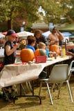 Les familles et les enfants découpent et peignent des potirons de Halloween Image libre de droits