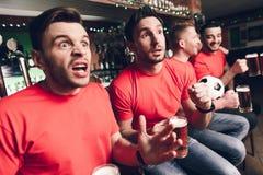 Les fans de foot gèlent dans le but de attente d'anticipation à la barre de sports photo libre de droits