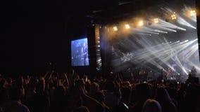 Les fans de foule battent des mains à la partie de musique en direct de roche contre la scène brillamment allumée avec de grands  banque de vidéos