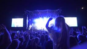 Les fans de foule ondulent des mains et font des photos sur le smartphone la soirée de musique en direct de roche contre l'étape  banque de vidéos