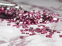 Les fausses pierres roses ont vers? d'une bouteille en verre sur une table de marbre images stock