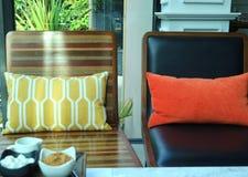 Les fauteuils confortables avec les coussins vifs de couleur et un condiment de café ont placé dans le premier plan images libres de droits