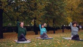 Les femelles décontractées s'asseyent sur des tapis de yoga dans la pose de visage de vache et étirent des bras tandis que l'inst banque de vidéos