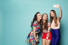 Les femmes à la mode dans le brigth vêtx faire la photo au téléphone intelligent Photo stock
