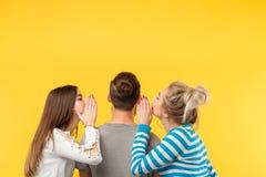 Les femmes adolescentes de vue arrière chuchotent que les secrets équipent jaune photos stock