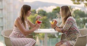Les femmes adultes gaies boivent un cocktail sur la terrasse d'hôtel banque de vidéos