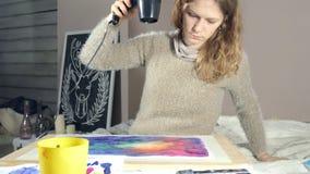 Les femmes adultes peignent avec les peintures colorées d'aquarelle et sèchent avec un sèche-cheveux dans une école d'art