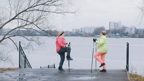 Les femmes agées en automne garent faire l'échauffement avant la marche nordique Photographie stock