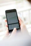 Les femmes analysent le marché boursier utilisant le téléphone intelligent Photos libres de droits
