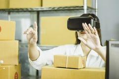 Les femmes asiatiques commencent le petit entrepreneur, main utilisant le vr pour communiquer, avec la boîte en carton pour les p images stock