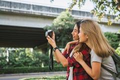 Les femmes asiatiques d'ami de beau voyageur heureux portent le sac à dos Femmes asiatiques de jeune ami employant l'appareil-pho Images libres de droits