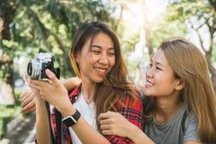 Les femmes asiatiques de jeune ami joyeux employant l'appareil-photo à faire la photo pendant la ville voyagent, des émotions gai Photo stock